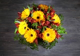 Wedding bouquet on wooden table . Bright yellow gerberas and red freesia. Top view