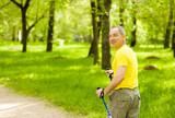 Senior man making nordic walking in the park