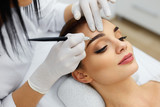 Beautician Doing Eyebrow Makeup Tattoo On Woman Using Machine