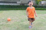 Happy asian boy playing football in the garden.