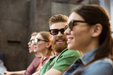 side view of concentrated and smiling friends in 3D glasses watching movie