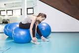 Young woman on pilates ball in the gym