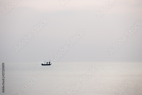 silhouette minimalist of single  fishery boat float on calm sea - 137230409