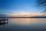 Sunset at Lake Starnberg, Germany. A jetty to the left, the silhouette of a tree to the right. Ducks in the water - partly blurred due to long time exposure.