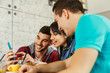 Group of young people having fun in cafe via smartphone