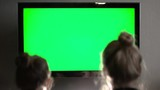 Two young long haired blond watching green TV screen and laughing
