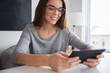 Smiling young Caucasian woman using digital tablet