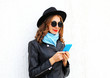 Fashion young woman using smartphone wearing a black rock jacket hat over white background