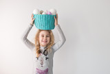 Little blonde girl holding basket with painted eggs. Easter day.