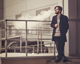 Young hipster man with a beard and glasses smokes an electronic cigarette. He stands at the business center. Youth fashion. Delicious pairs. Cloud of steam.