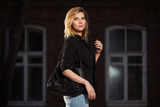 Young fashion blond business woman with handbag walking in night on city street