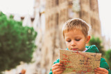 spain travel - little boy looking at map in Barcelona