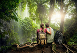 Fototapety Couple hikers with backpacks enjoying view waterfall in rain forest