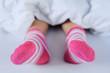 Füße mit bunten Socken unter der Bettdecke