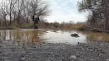 A cyclist rides through a puddle