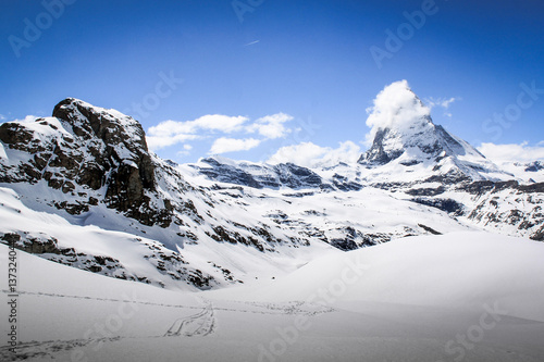 Poster Scenic view on snowy Matterhorn peak in sunny day with blue sky and some clouds in background, Switzerland