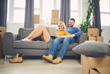 couple in new apartment using laptop. Lot of moving boxes around them