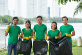 Portrait of Asian man and woman in green T-shirts and rubber gloves posing for photography while holding garbage plastic bags in hands