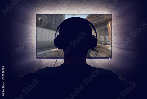 Gamer in headphones sits in front of a blank monitor in dark room Poster