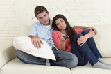 couple watching television together at home sofa couch looking bored frustrated switching channels