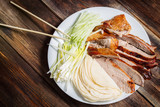 Peking Duck - Chinese roast duck with cucumber pieces, onion, pancakes on white plate close up. Wooden table and top view