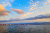 Beautiful morning seascape. Bright blue sky with cumulus clouds and a calm sea. The mountains and the city on the horizon. Dawn above the sea.