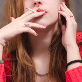 Detail of ther young modern girl holding and smoking cigarette