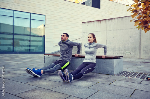 couple doing triceps dip exercise outdoors - 137387094