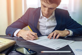 Man businessman signs documents with a pen