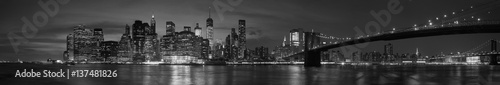 Tuinposter New York New York city with Brooklyn Bridge, iconic skyline panorama at night in black and white