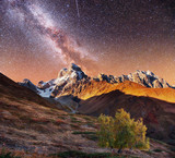 Fantastic collage. Starry sky above snow-capped mountain peaks.