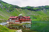Photo of balea lake in fagaras green mountains at sunset, red house with fog near a lake with reflection, Romania.