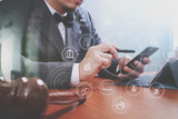 Justice and Law context.Male lawyer hand working with smart phone,digital tablet computer docking keyboard with gavel and document on wood table,virtual interface graphic icons diagram - 137515296