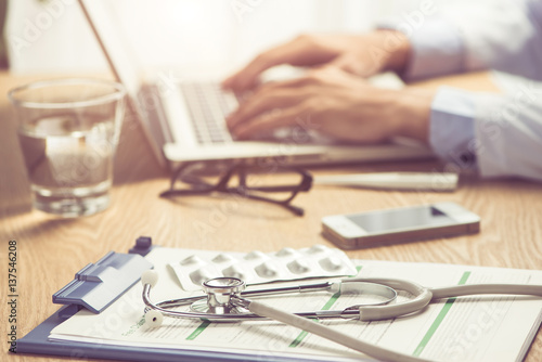 Male doctor working at wooden desk in clinic