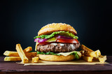 Fototapety Craft beef burger and french fries on wooden table isolated on dark background.