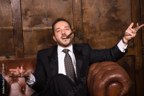 Rich businessman with cigar sitting on sofa and looking at camera Poster