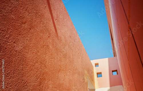 view of the sky from a narrow passage between the orange houses