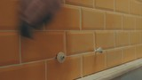 Mans hand washed away the remnants of putty from orange tiles on the wall