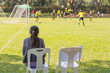 woman watching a school boy soccer game on a sunny day