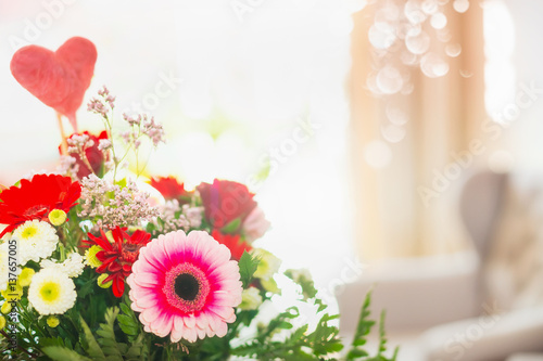 Close up of  flowers bunch with heart in room with light and bokeh