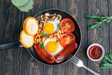 Breakfast tomatoes, sausages, beans, mushrooms, eggs,toast and herbs top view