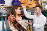 Friendly smiling  shopgirl helping male client to select guitar
