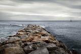 Camino de rocas en el mar y faro en el horizonte