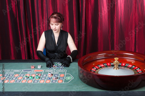 young woman wearing  black gloves and black dress parlays in a casino Obraz na płótnie