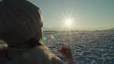 Child girl make hands heart around sun at sunset in mountains