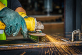 worker hand working by Electric grinder industry tool cutting steel with split fire use for industrial manufacturing theme , Selective focus