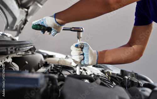 Mechanic working in auto repair garage. Car maintenance - 137696208