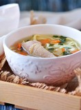 Soup with homemade noodles and organic chicken with carrots, root and leaves of parsley, onion and celery sticks.