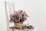 flowers in a basket on vintage chair