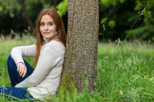 Poster Beautiful Young Woman Sitting Leaning Against Tree